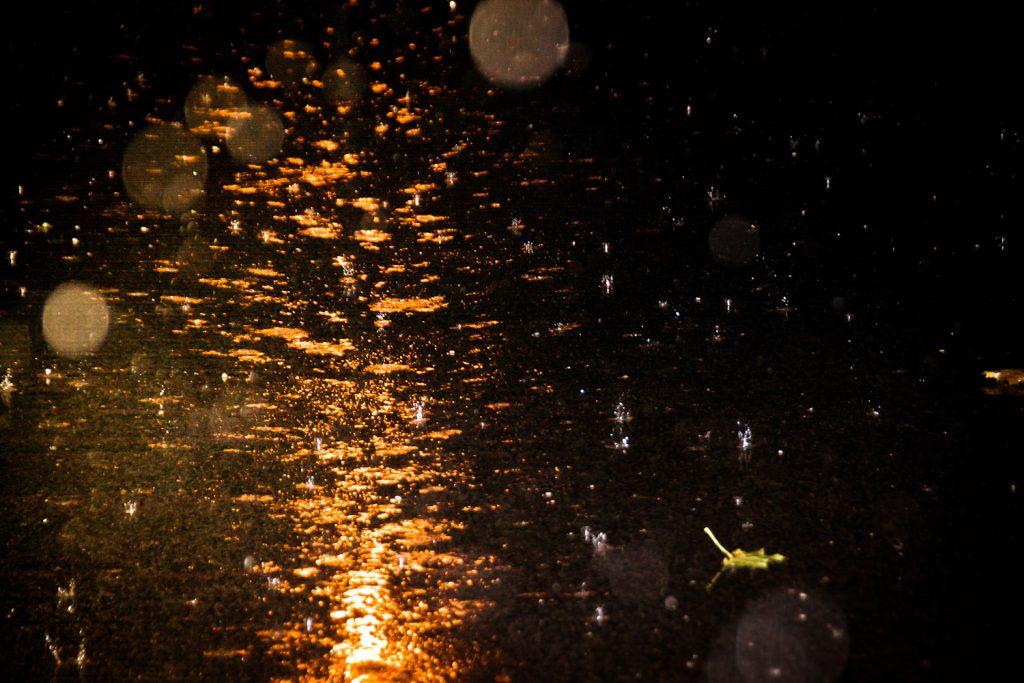 Starker Regenfall bei Dunkelheit am Parkplatz: angeblitzt