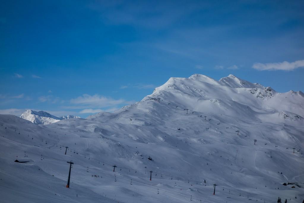 Während das Skigebiet noch im Schatten liegt, werden die ersten Gipfel schon von der Sonne angeschienen