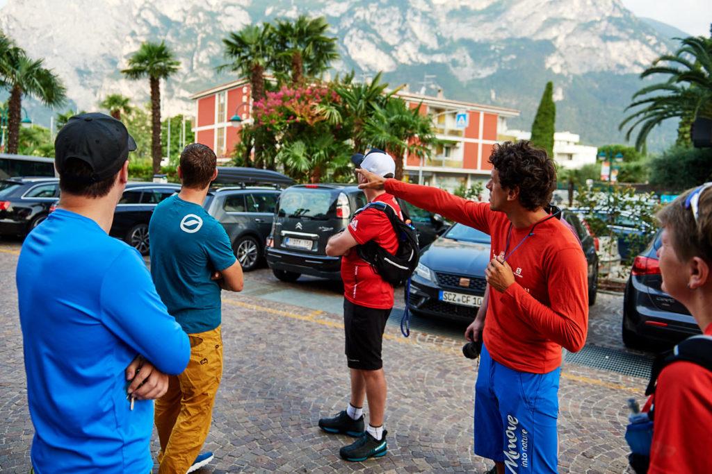 Matteo Guardini zeigt, noch am Lakefront Hotel Mirage, das erste Mal das heutige Ziel – den Cima Capi